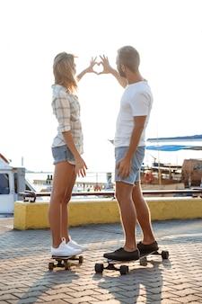 Joven pareja hermosa caminando a orilla del mar, mostrando corazón, skate