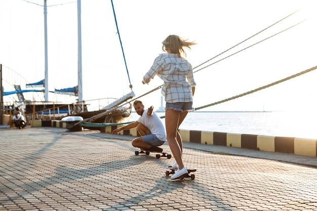 Joven pareja hermosa caminando en la playa, el skate.