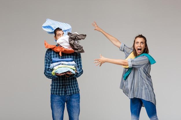 Joven pareja hermosa celebración lavar la ropa, peleando por la pared gris