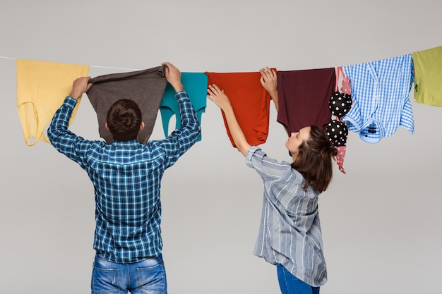 Joven pareja hermosa colgando lavar la ropa sobre la pared gris