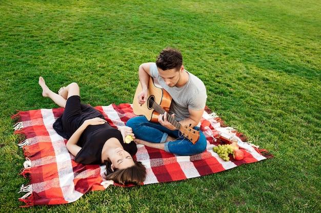 Joven pareja hermosa descansando en el parque