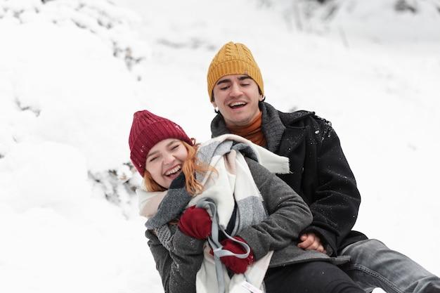 Joven pareja hermosa divirtiéndose en invierno