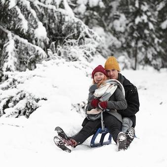 Joven pareja hermosa divirtiéndose sentado en el trineo