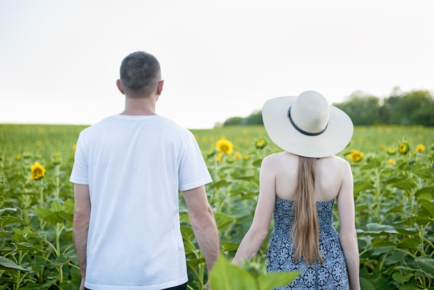Joven pareja hermosa se encuentra cogidos de la mano contra el campo verde de girasoles florecientes. vista trasera