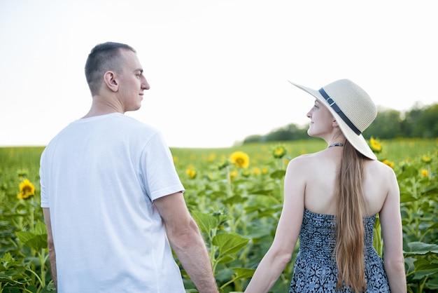 Joven pareja hermosa se encuentra cogidos de la mano y mirándose el uno al otro contra el campo verde de girasoles florecientes