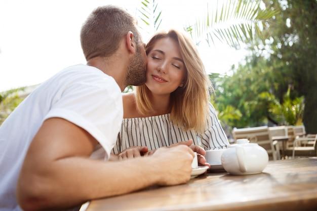 Joven pareja hermosa hablando, sonriendo, descansando en la cafetería.
