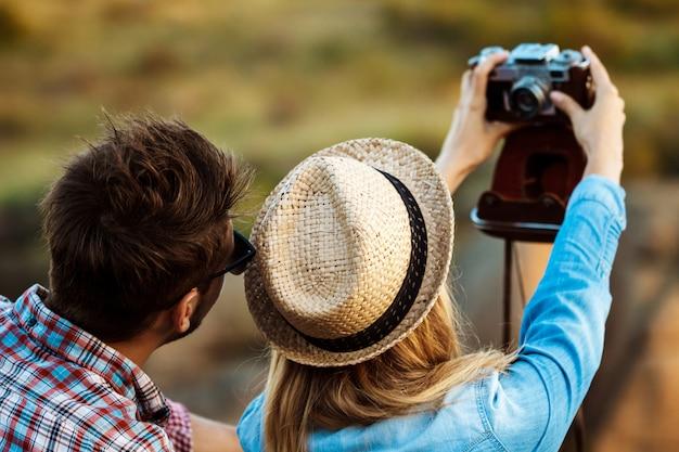 Joven pareja hermosa haciendo selfie en cámara vieja, fondo del cañón