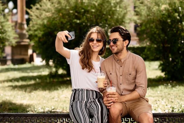 Joven pareja hermosa haciendo selfies en la calle