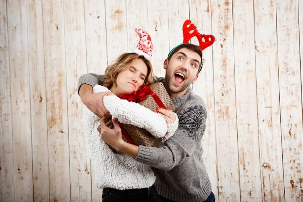 Joven pareja hermosa luchando por el regalo de navidad sobre pared de madera