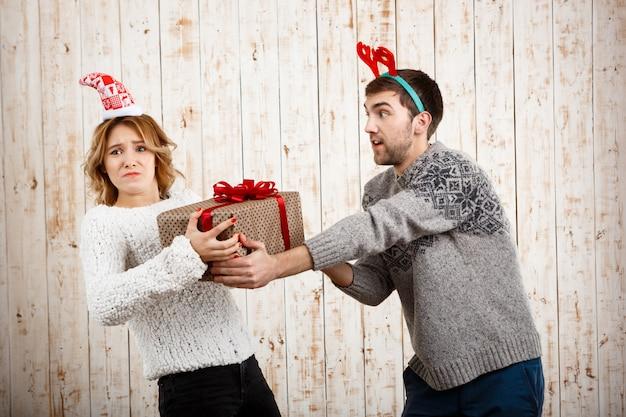 Joven pareja hermosa luchando por el regalo de navidad sobre superficie de madera