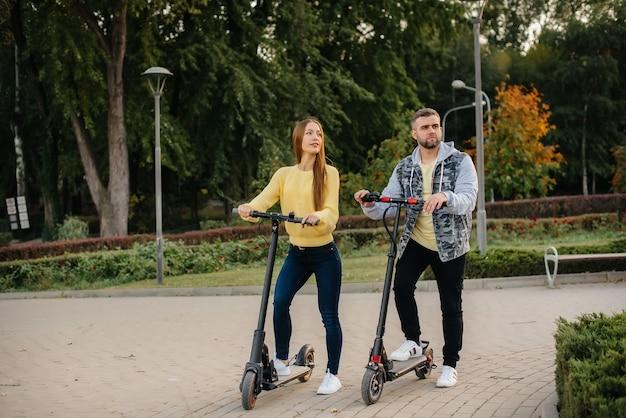 Una joven pareja hermosa monta scooters eléctricos en el parque en un cálido día de otoño. aficiones y recreación.