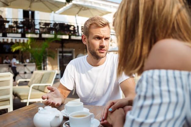 Joven pareja hermosa pelea, sentado en la cafetería.
