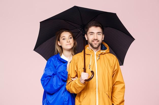 Joven pareja hermosa posando en abrigos de lluvia con paraguas sobre pared rosa claro