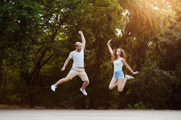 Joven pareja hermosa saltando, sonriendo, regocijándose, caminando en el parque.