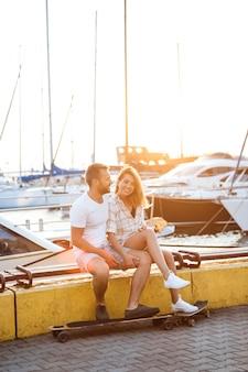 Joven pareja hermosa sentada en la playa, sonriendo, andar en monopatín.