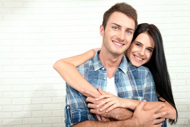 Joven pareja hermosa sonriendo y abrazando