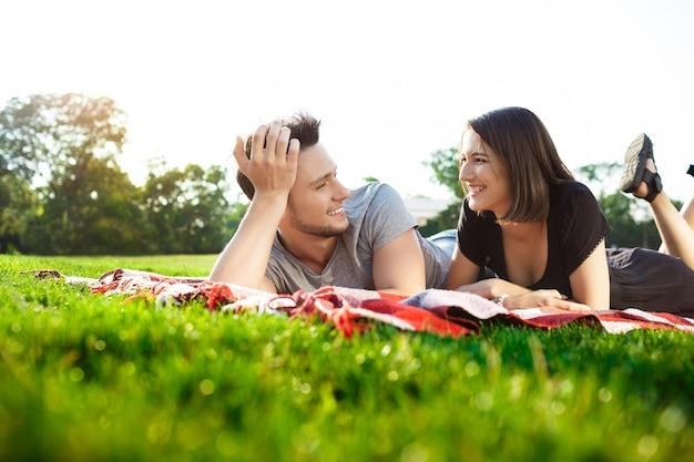 Joven pareja hermosa sonriendo, descansando en un picnic en el parque.