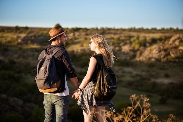 Joven pareja hermosa sonriendo, mirándose en el cañón