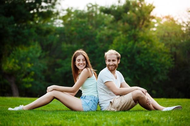 Joven pareja hermosa sonriendo, sentado en el césped en el parque.