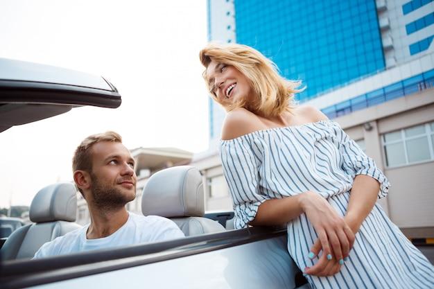 Joven pareja hermosa sonriendo, sentado en el coche cerca del mar.