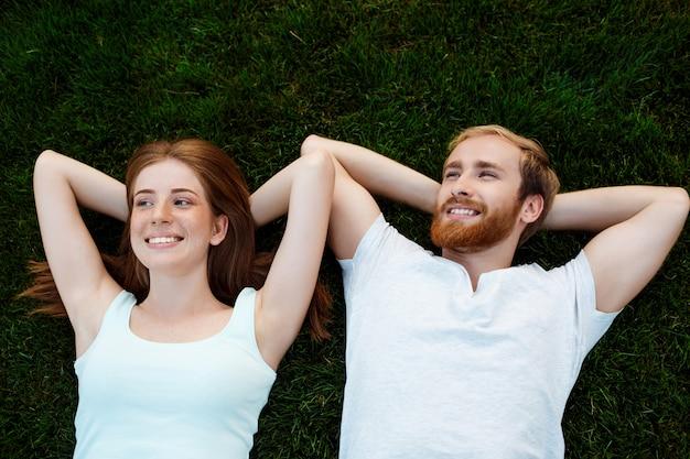 Joven pareja hermosa sonriendo, tumbado en la hierba en el parque. disparo desde arriba.