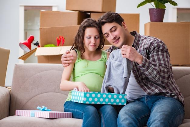Joven pareja de hombre y mujer embarazada con caja de regalo