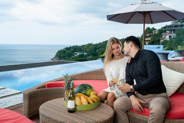 Joven pareja en un hotel de lujo cerca de la piscina infinita degustando una copa de vino blanco
