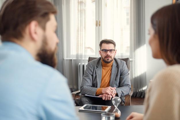 Joven pareja infeliz en sesión especial de terapia de matrimonio con terapeuta profesional. psicólogo calificado escucha los problemas familiares de la joven pareja infeliz.