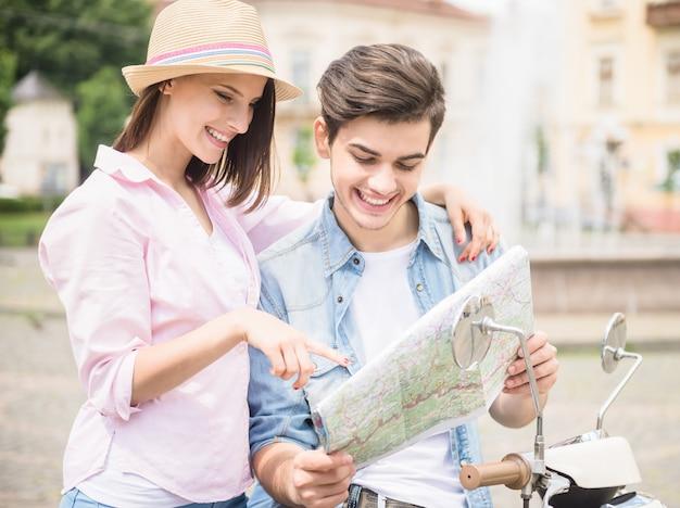 Joven pareja ingeniosa sentado en scooter y leer el mapa.