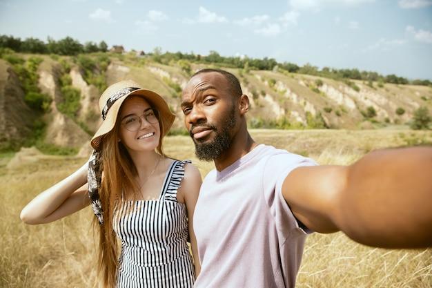 Joven pareja internacional multiétnica al aire libre en la pradera en un día soleado de verano. hombre afroamericano y mujer caucásica haciendo picnic juntos. concepto de relación, verano. haciendo selfie.