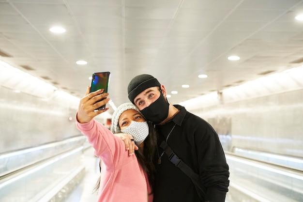 Una joven pareja interracial de amantes con máscaras y gorros de lana haciendo un selfie en un pasillo del metro o del aeropuerto.