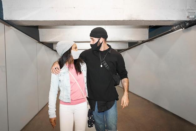 Joven pareja interracial de amantes en un pasillo del metro subterráneo con máscaras faciales