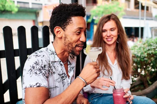 Joven pareja interracial en el amor bebiendo un cóctel en el bar en verano