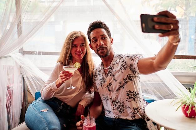 Joven pareja interracial en el amor tomando selfie en el bar