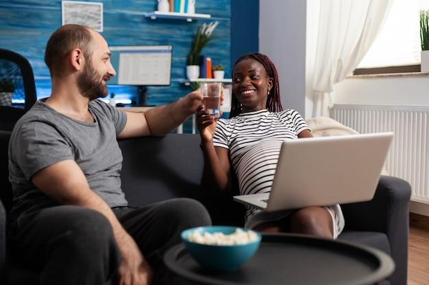 Joven pareja interracial esperando un niño en casa con el dispositivo. hombre caucásico que lleva un vaso de agua a la madre afroamericana embarazada con portátil. personas de raza mixta con embarazo