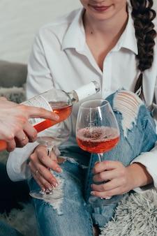 Una joven pareja en jeans y camisas blancas bebe vino rosado