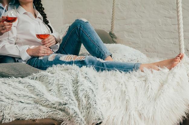 Una joven pareja en jeans con vino en una cama