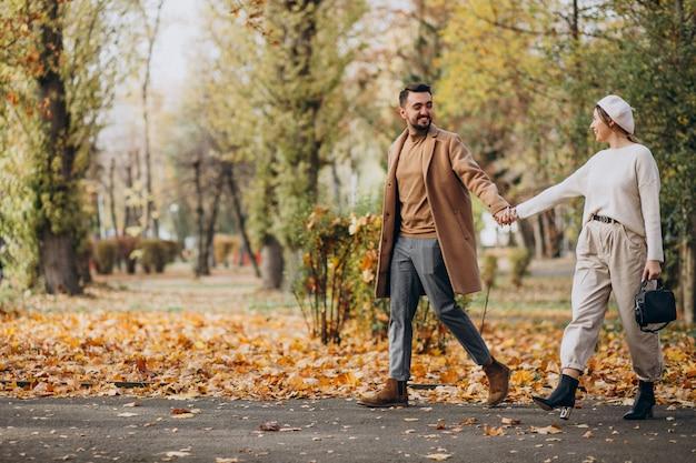 Joven pareja junto en un parque de otoño