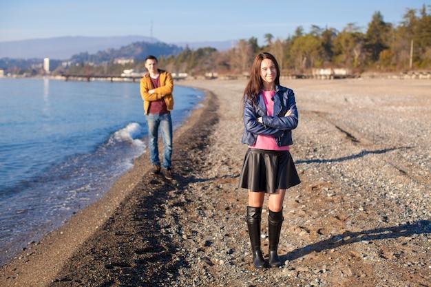 Joven pareja junto en una playa vacía en día de invierno
