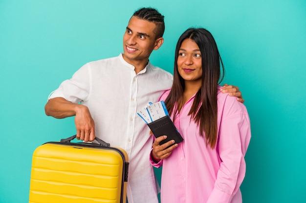 Joven pareja latina que va a viajar aislado sobre fondo azul se ve a un lado sonriente, alegre y agradable.