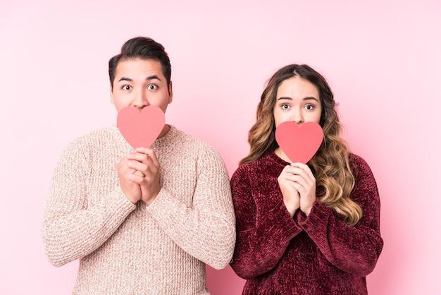Joven pareja latina sosteniendo un corazón pegatina