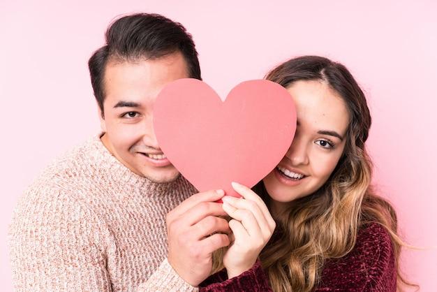 Joven pareja latina sosteniendo una pegatina de corazón