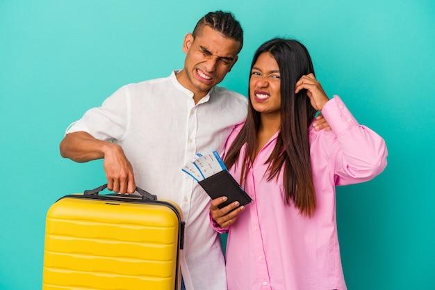 Joven pareja latina va a viajar aislado sobre fondo azul cubriendo las orejas con las manos.
