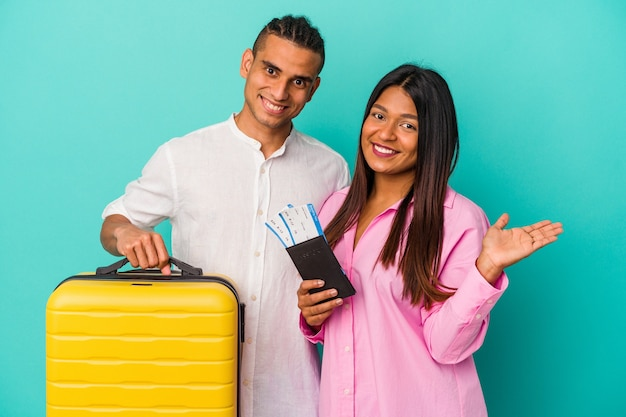 Joven pareja latina va a viajar aislado sobre fondo azul mostrando un espacio de copia en una palma y sosteniendo otra mano en la cintura.