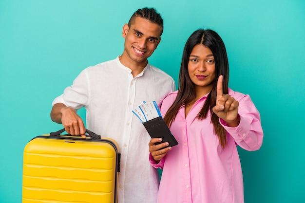 Joven pareja latina va a viajar aislado sobre fondo azul mostrando el número uno con el dedo.
