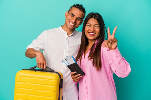 Joven pareja latina va a viajar aislado sobre fondo azul mostrando el número dos con los dedos.