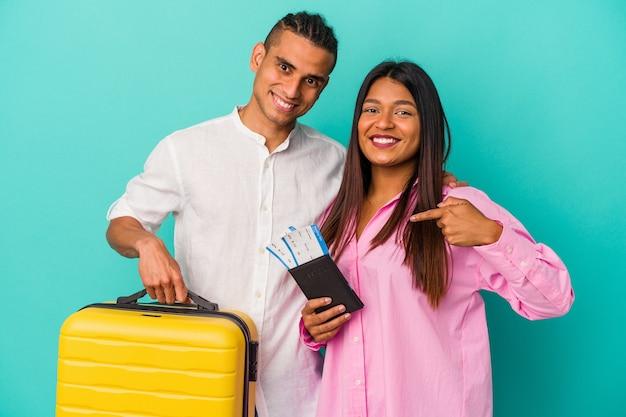 Joven pareja latina va a viajar aislado sobre fondo azul persona apuntando con la mano a un espacio de copia de camisa, orgulloso y seguro