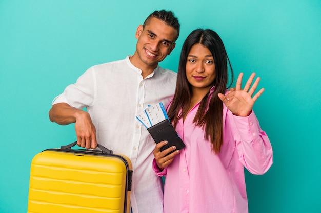 Joven pareja latina va a viajar aislado sobre fondo azul sonriendo alegre mostrando el número cinco con los dedos.