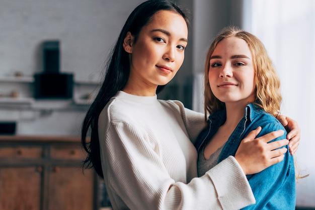 Joven pareja de lesbianas abrazando en casa