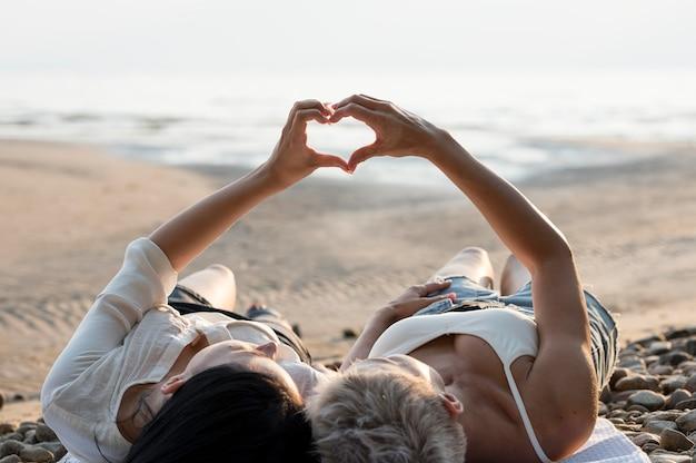 Joven pareja de lesbianas formando la mano en forma de corazón